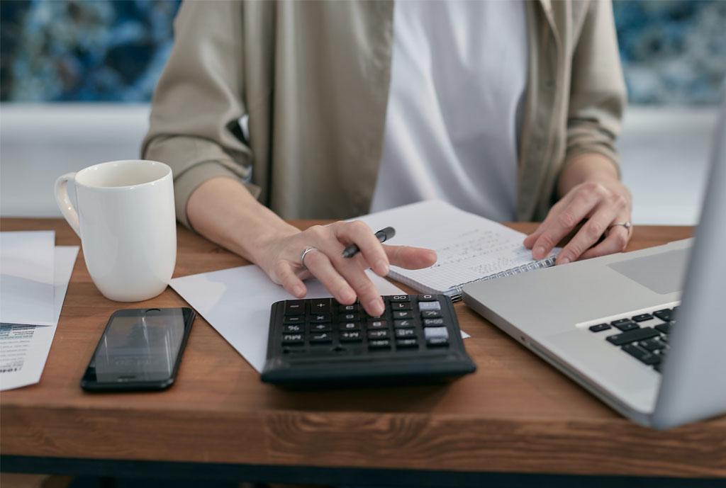 femme avec calculatrice et ordinateur