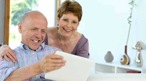 Couple souriant devant une tablette