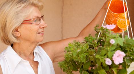 Femme âgée arrosant les plantes de sa résidence séniors
